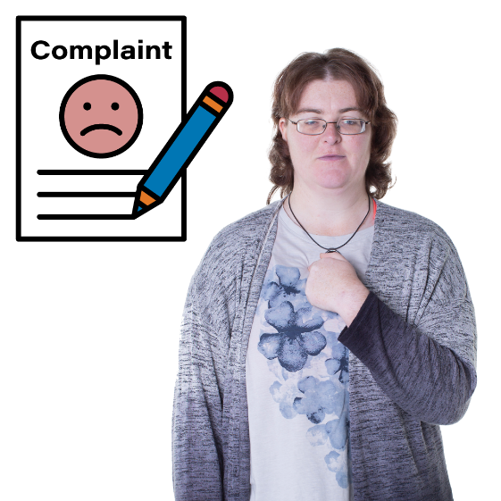 A woman pointing at herself with a complaints document next to her